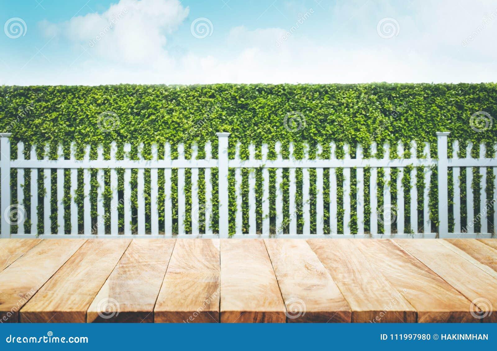 Tampo da mesa de madeira no borrão da cerca e do fundo brancos do jardim