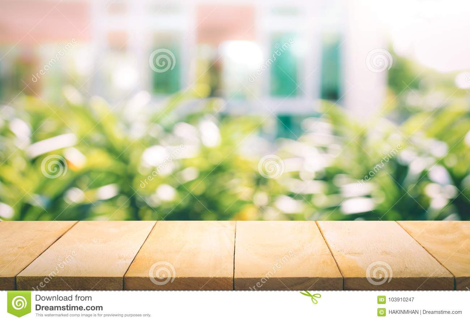 Tampo da mesa de madeira no borrão da janela com fundo da flor do jardim