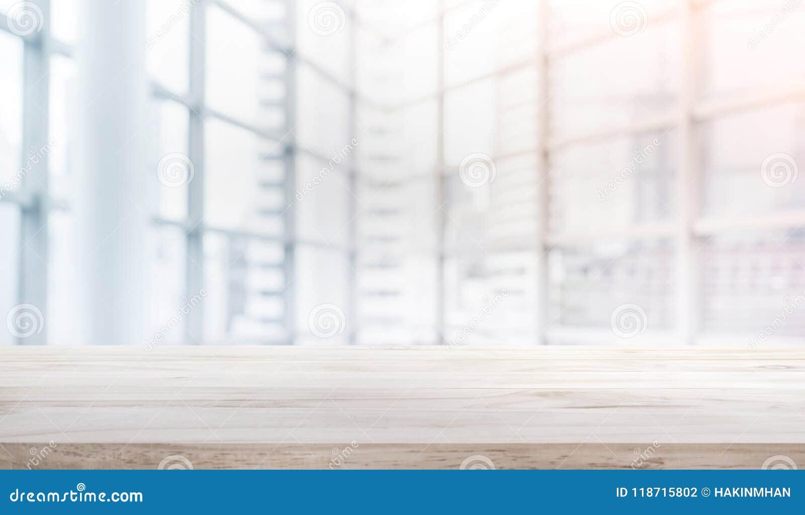 Tampo da mesa de madeira no escritório branco do formulário do fundo da janela de vidro do borrão