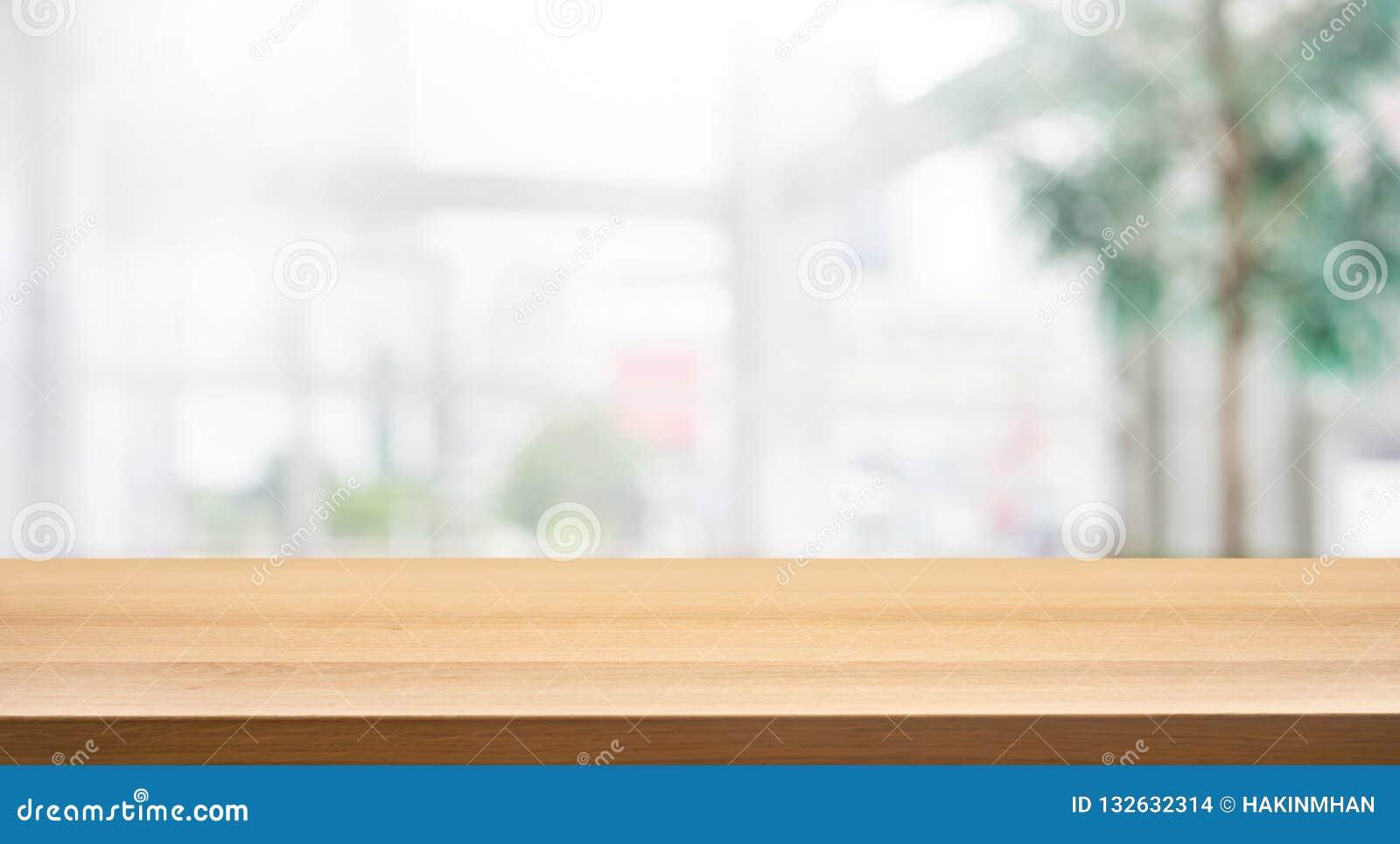 Tampo da mesa de madeira no prédio de escritórios branco do formulário do fundo da parede de vidro do borrão