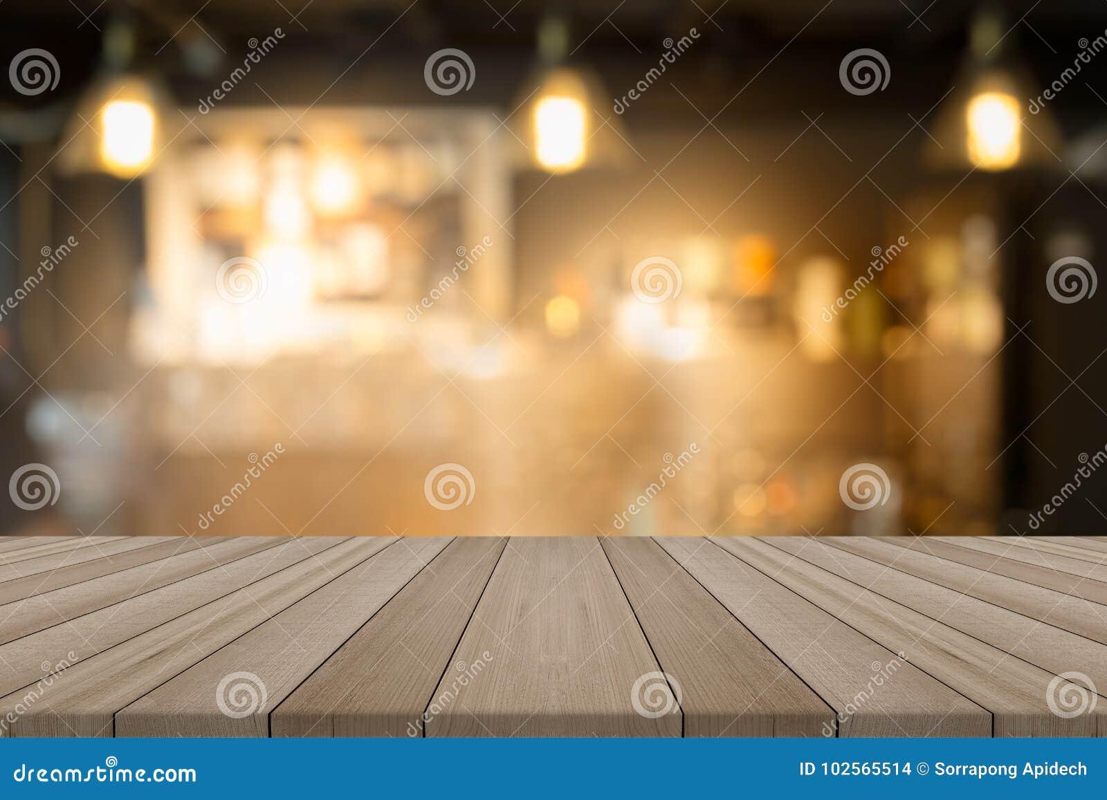 Tampo da mesa de madeira vazio na cafetaria borrada do formulário do fundo