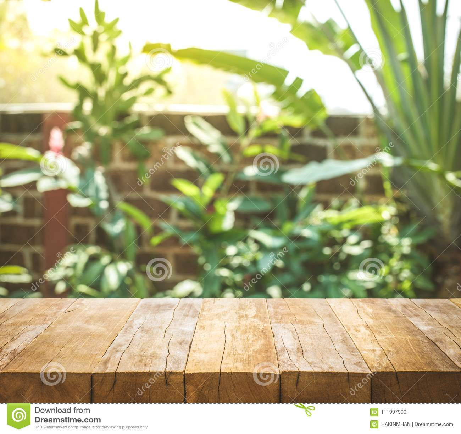 Tampo da mesa de madeira vazio no fundo do jardim e da casa do sumário do borrão