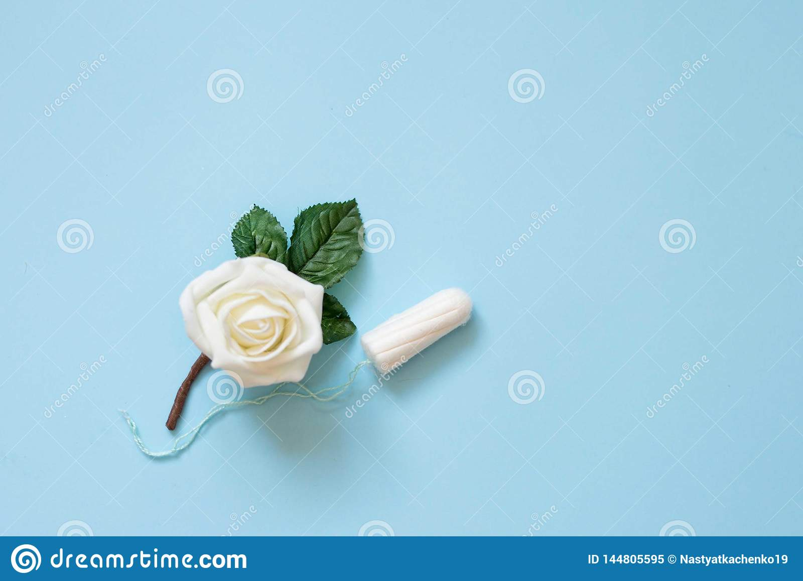 Tampon menstrual cotton pads on blue background with white flower . Woman hygiene conception photo. Soft tender protection for
