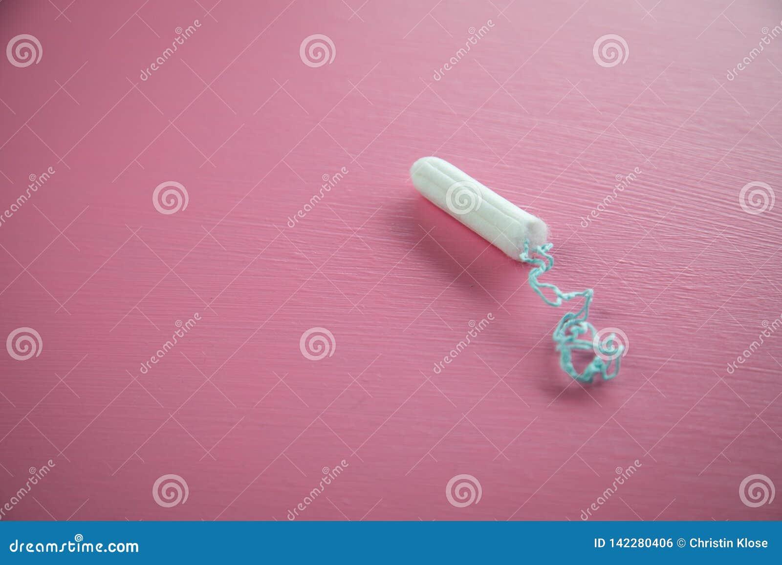 Tampon op roze achtergrond voor vrouwelijke persoonlijke hygiëne en bescherming tijdens de cyclus van de menstruatieperiode