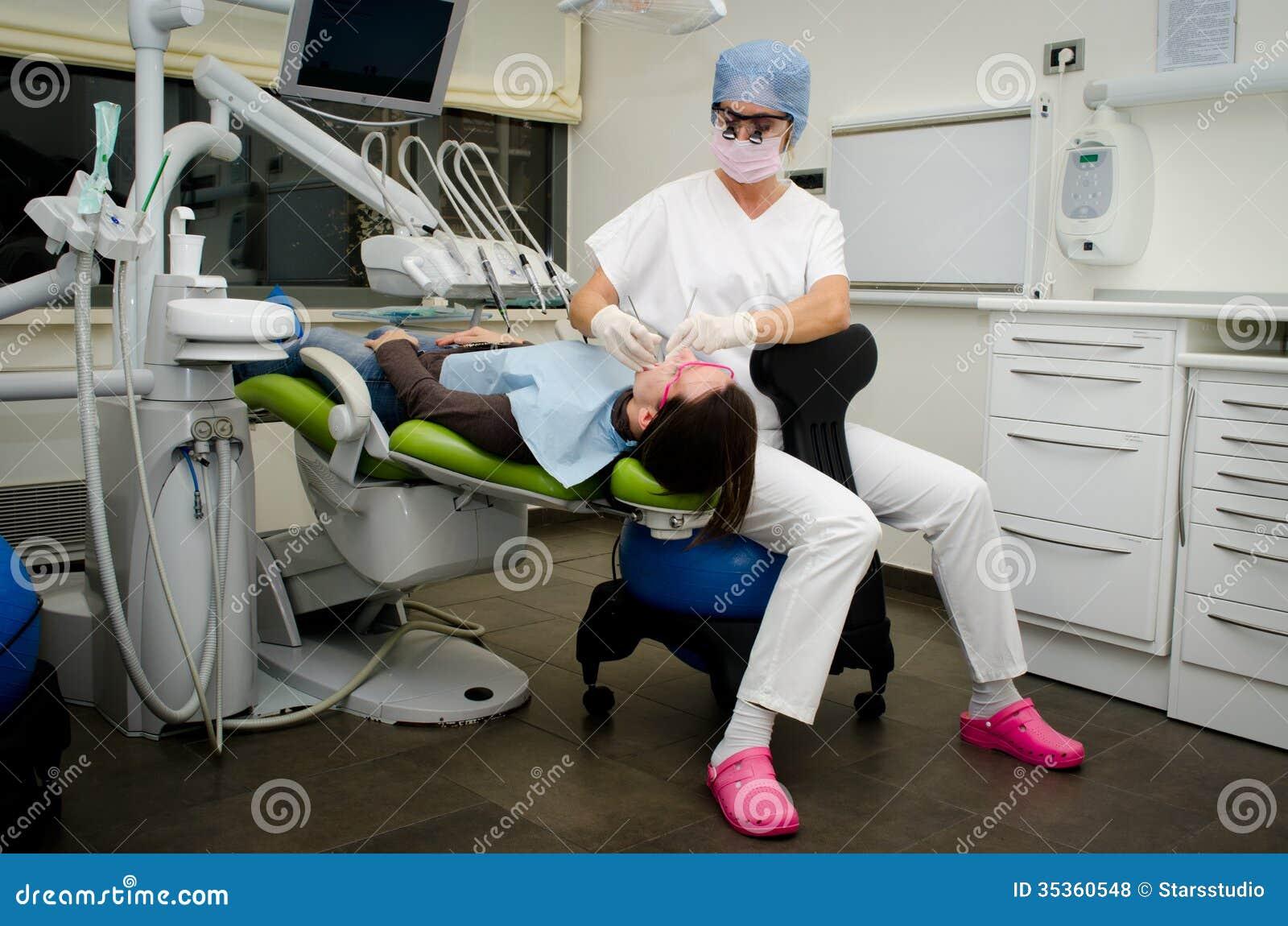 Tandarts die aan patiënt in tandkliniek werken