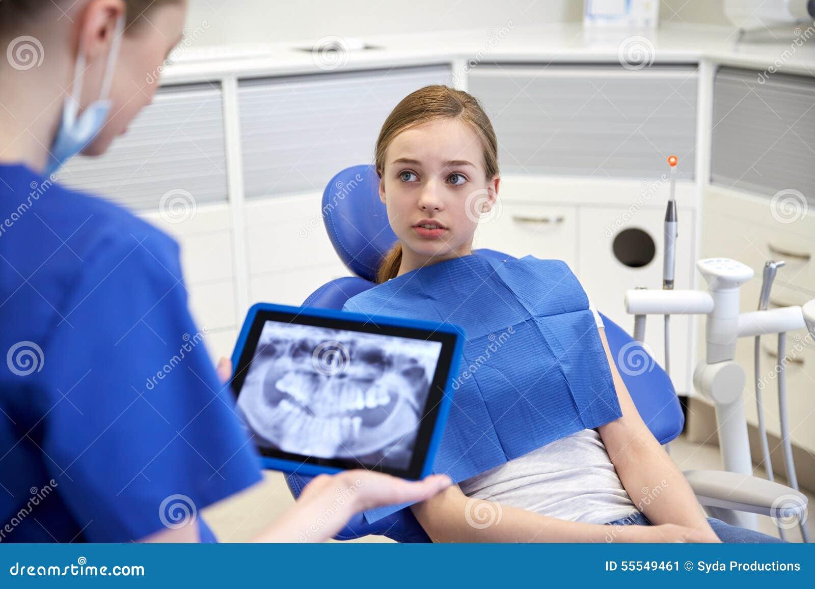 Tandarts die röntgenstraal op tabletpc tonen aan geduldig meisje