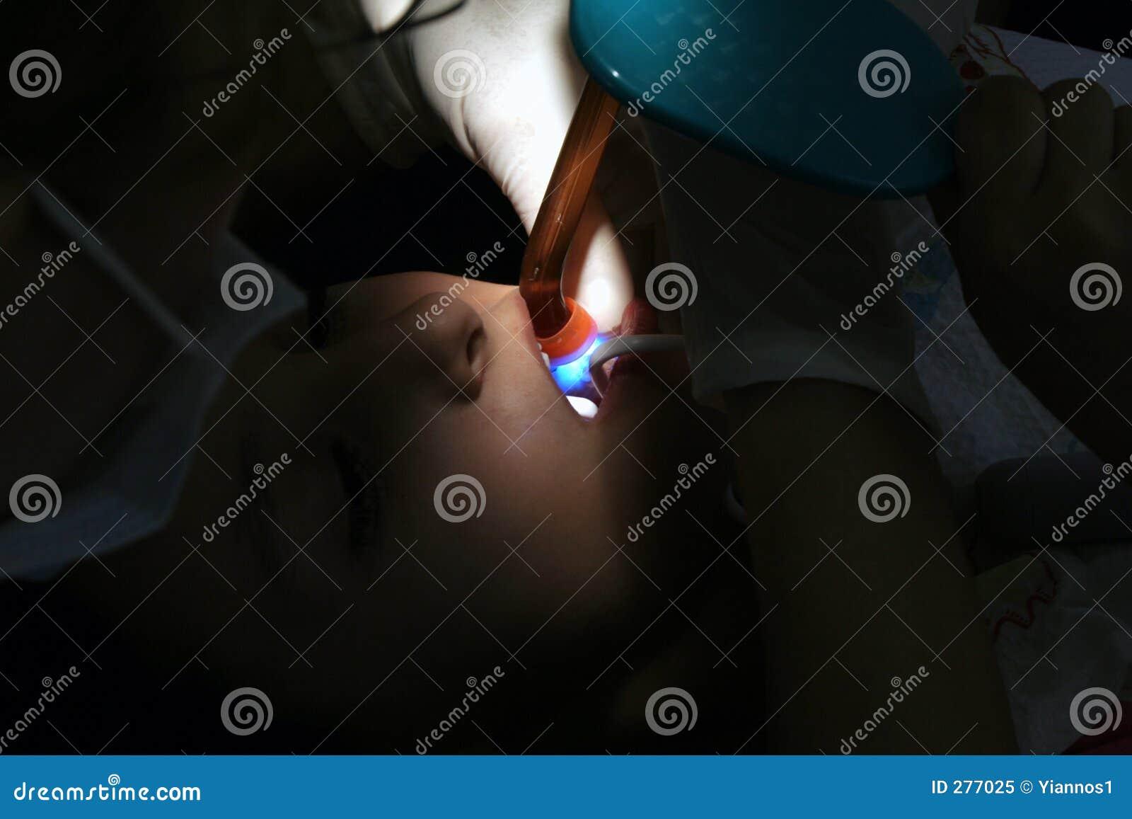 Tandarts die zorg neemt die ultraviolette stralen gebruikt