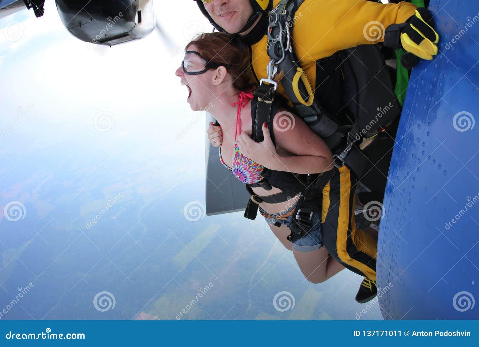 Tandem skydiving. Exit. Girl is screaming.