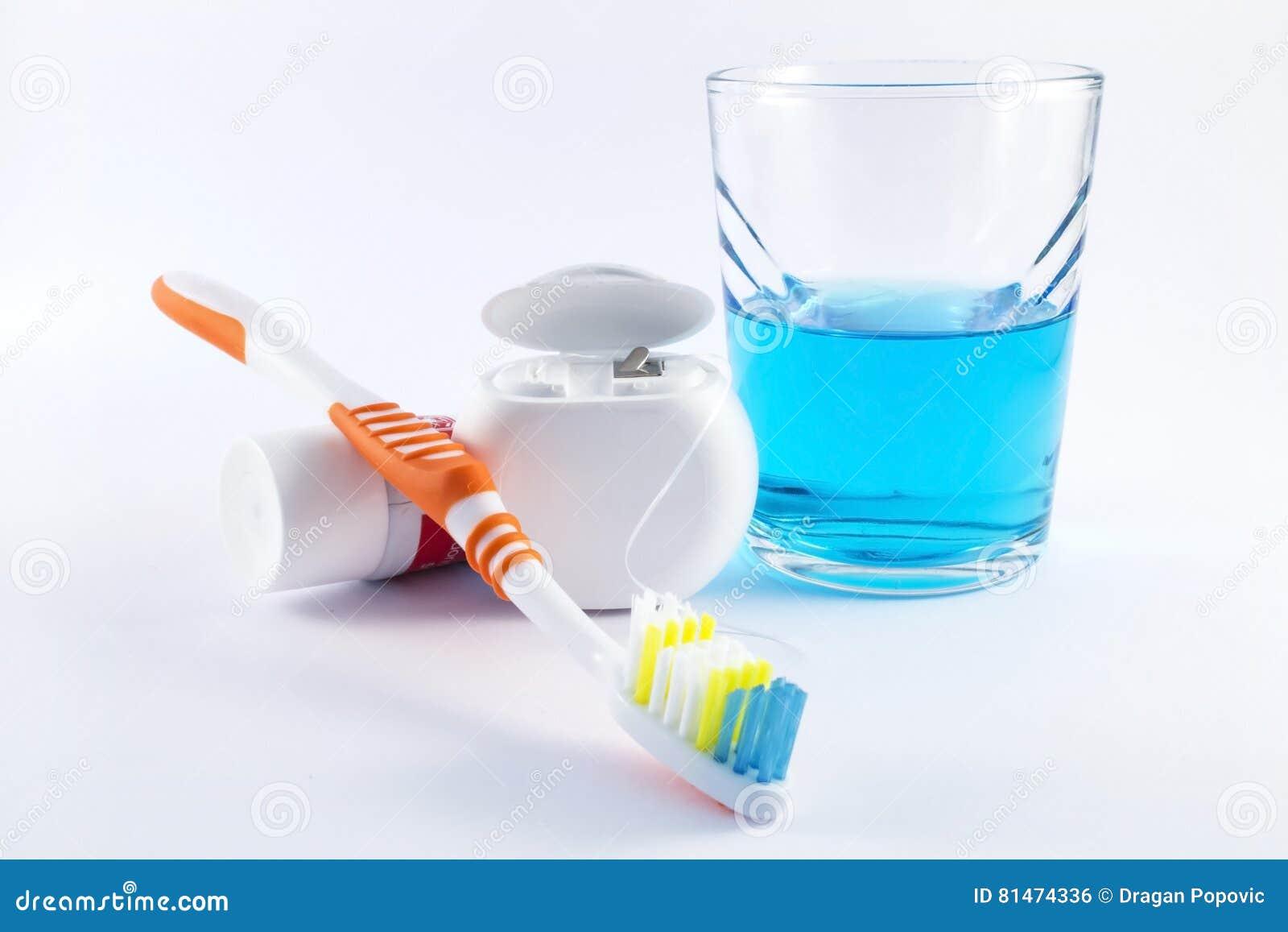 Tandenborstel, tandzijde, tandpasta en mondspoeling op witte achtergrond
