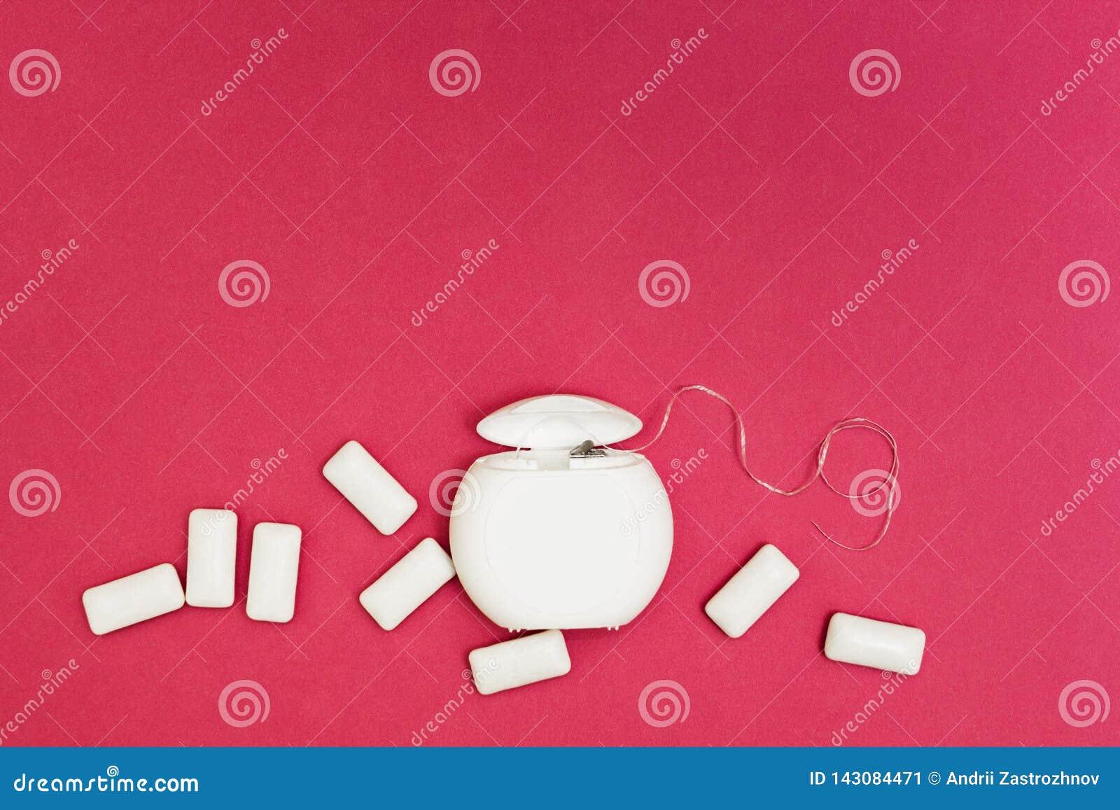 Tandzijde en kauwgomstootkussens op een roze achtergrond, ruimte voor tekst