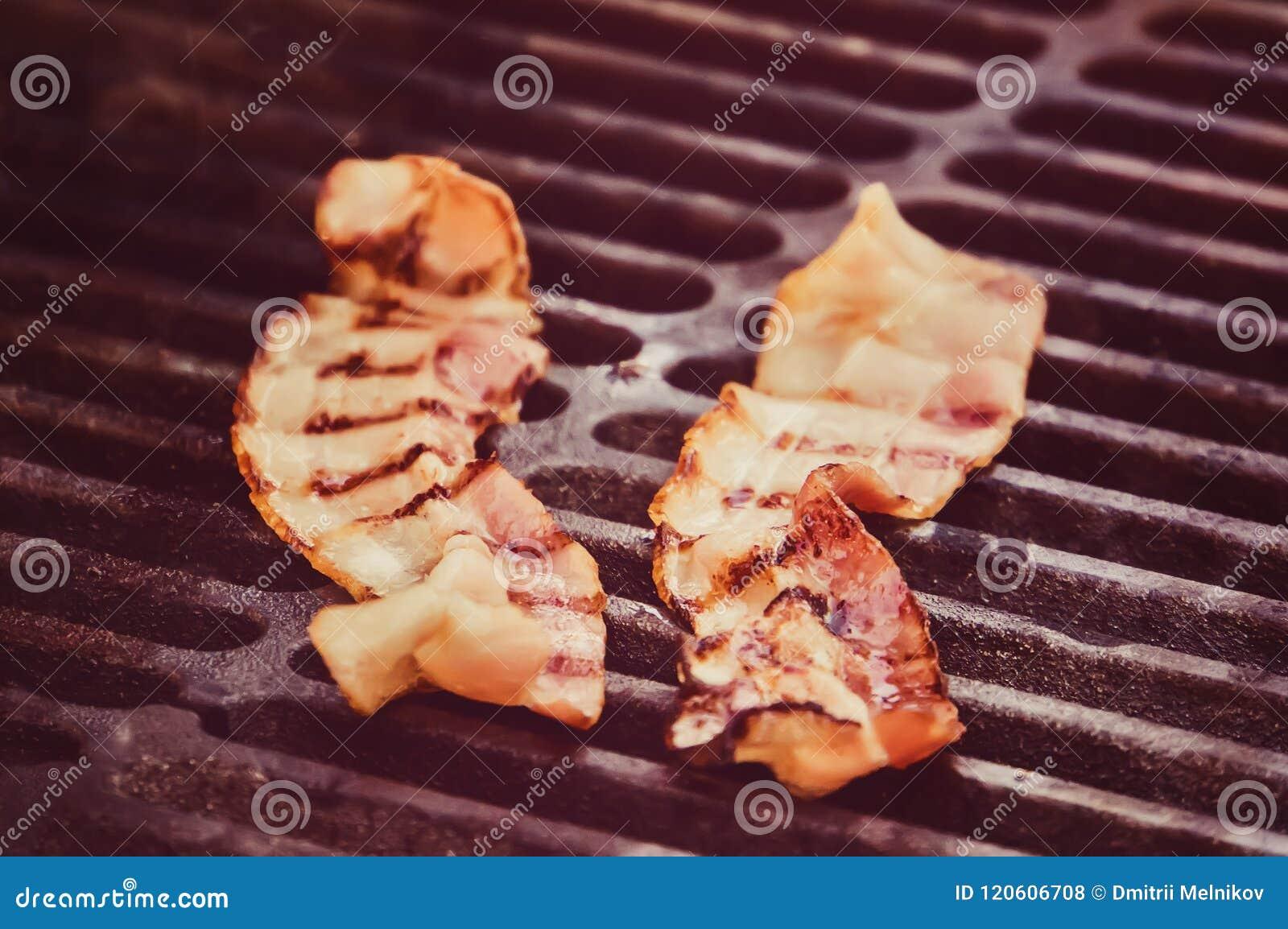 Tang die de knapperige gerookte geroosterde plak van het barbecuebacon houden,