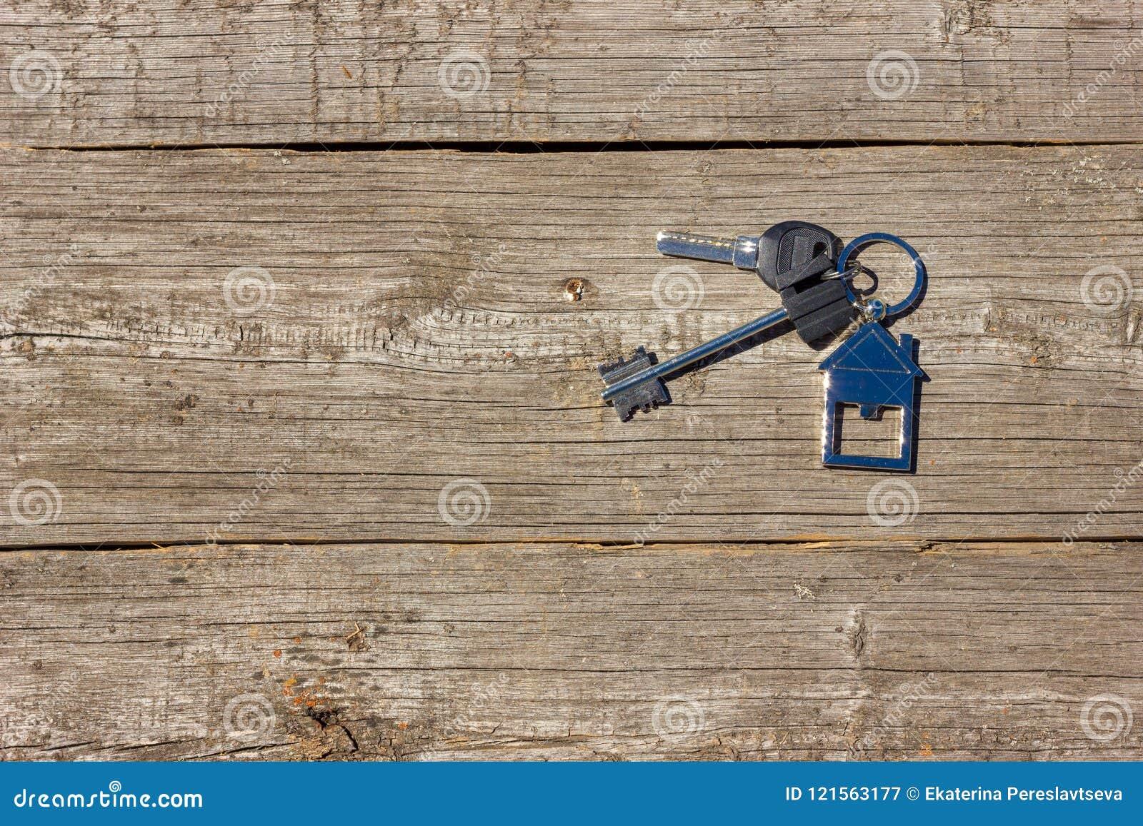 Tangenterna till huset ligger på en träbakgrund, begreppet av att köpa en egenskap