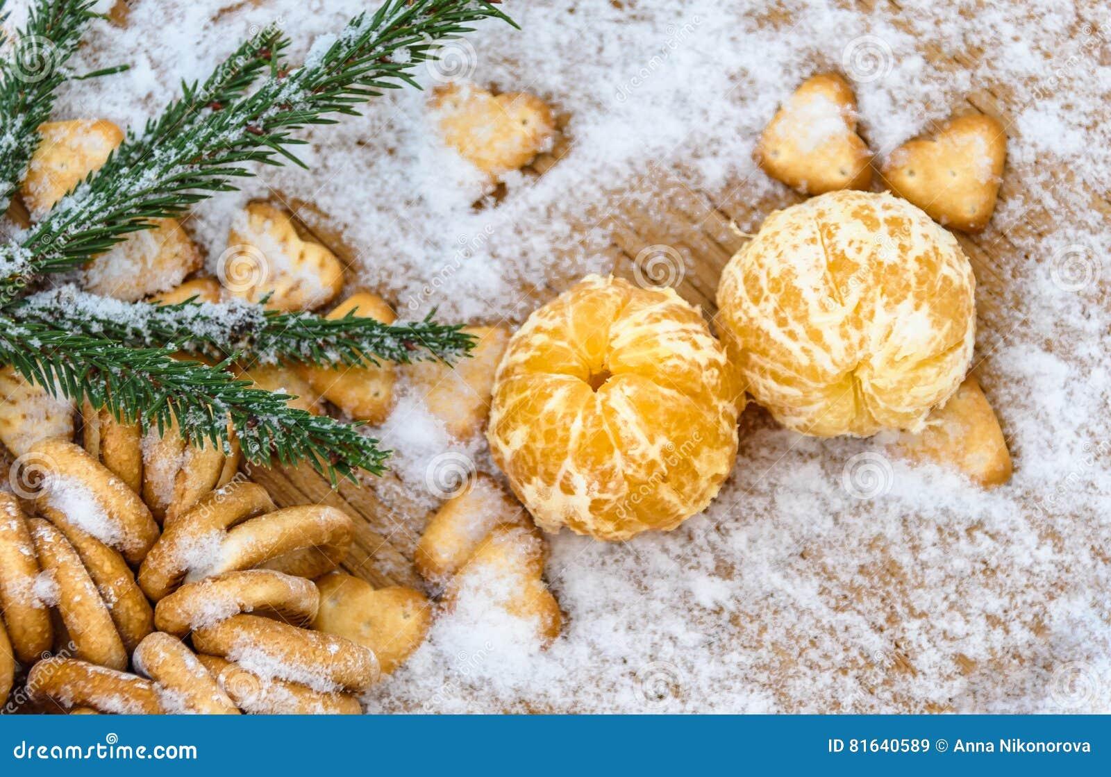 Tangerinas na neve em uma tabela de madeira, ano novo, uma vida imóvel