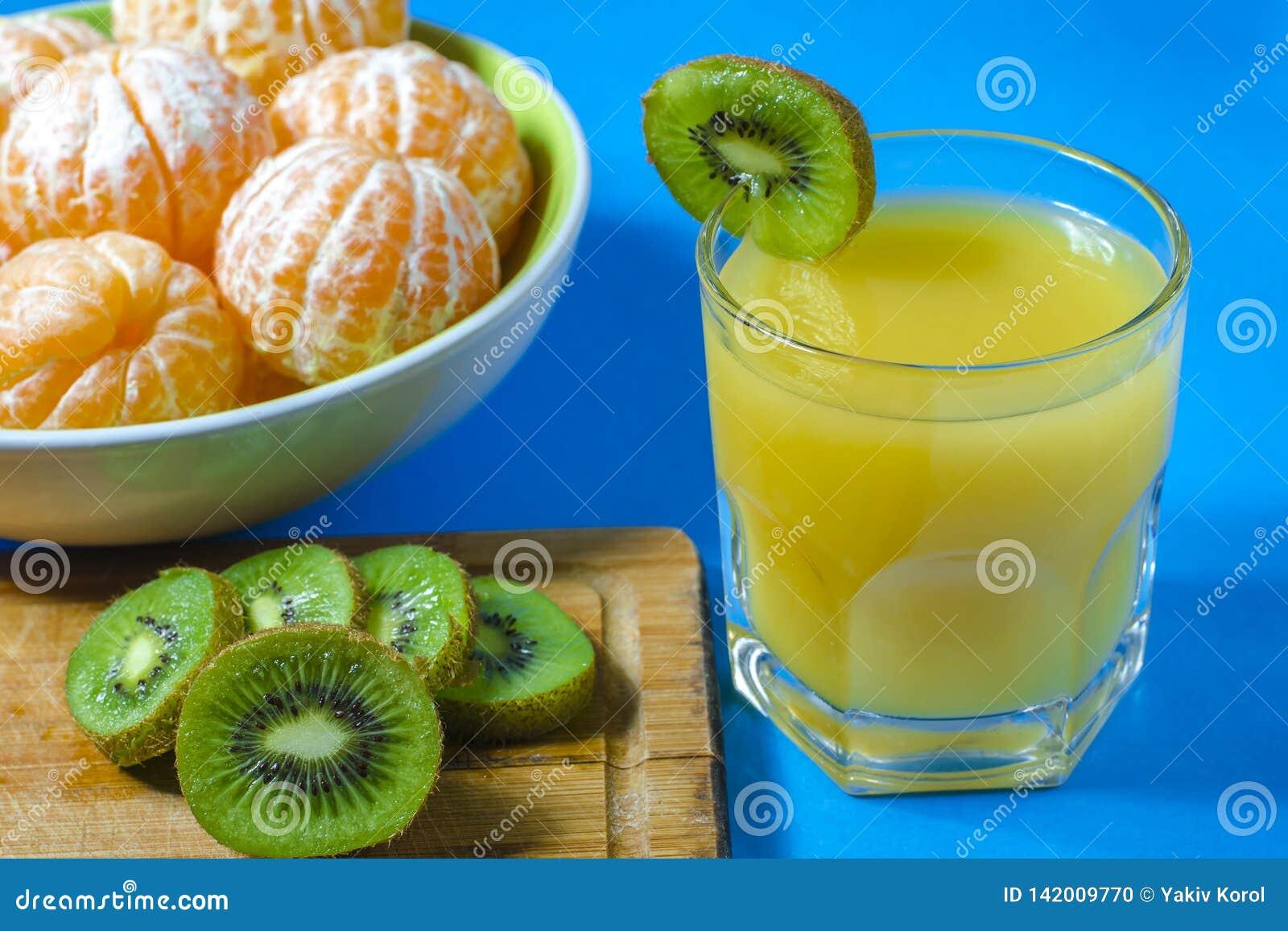 Tangerines и киви стеклянный политый сок голубая предпосылка, конец-вверх