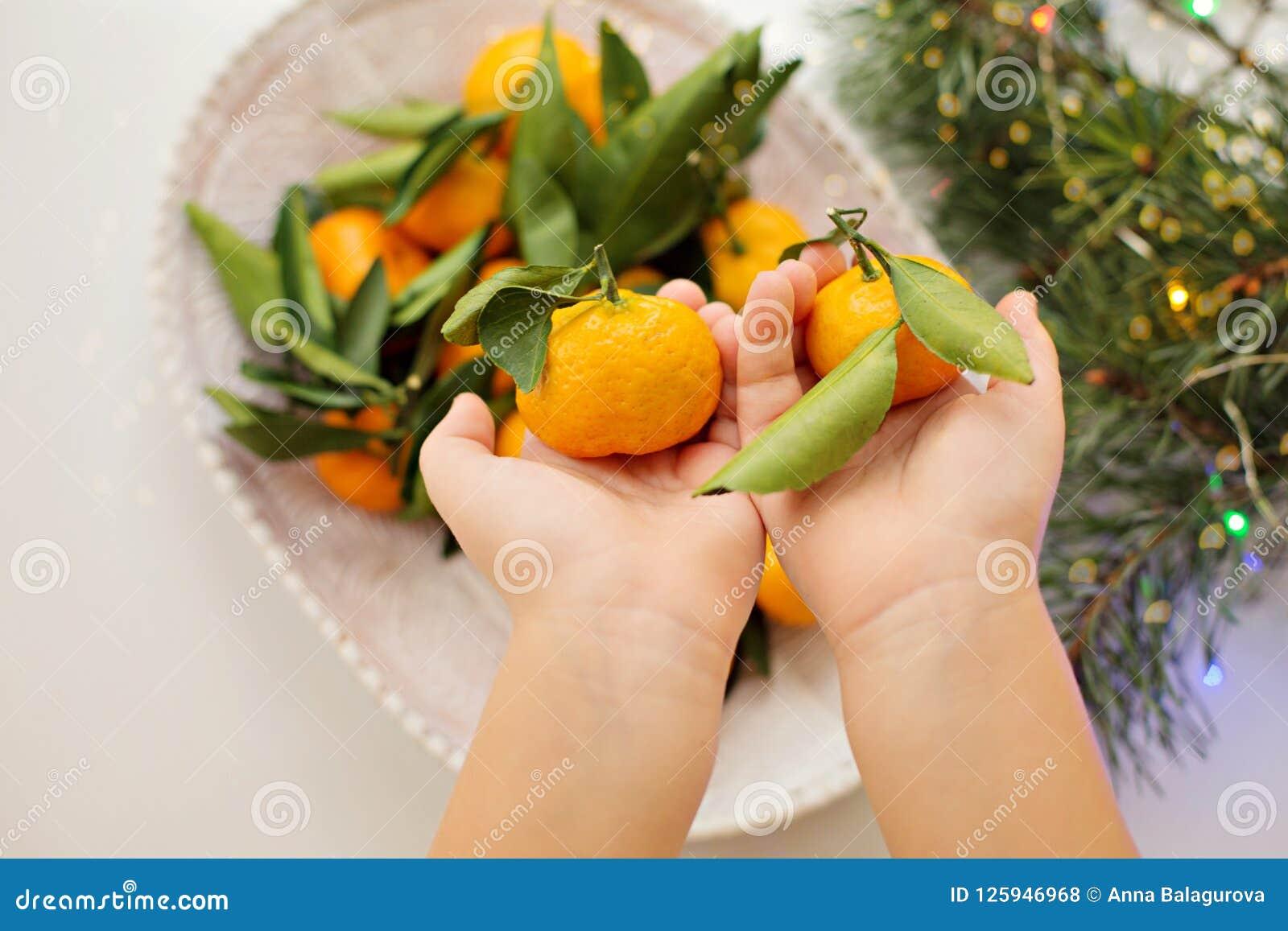 Tangerines в руках ` s детей