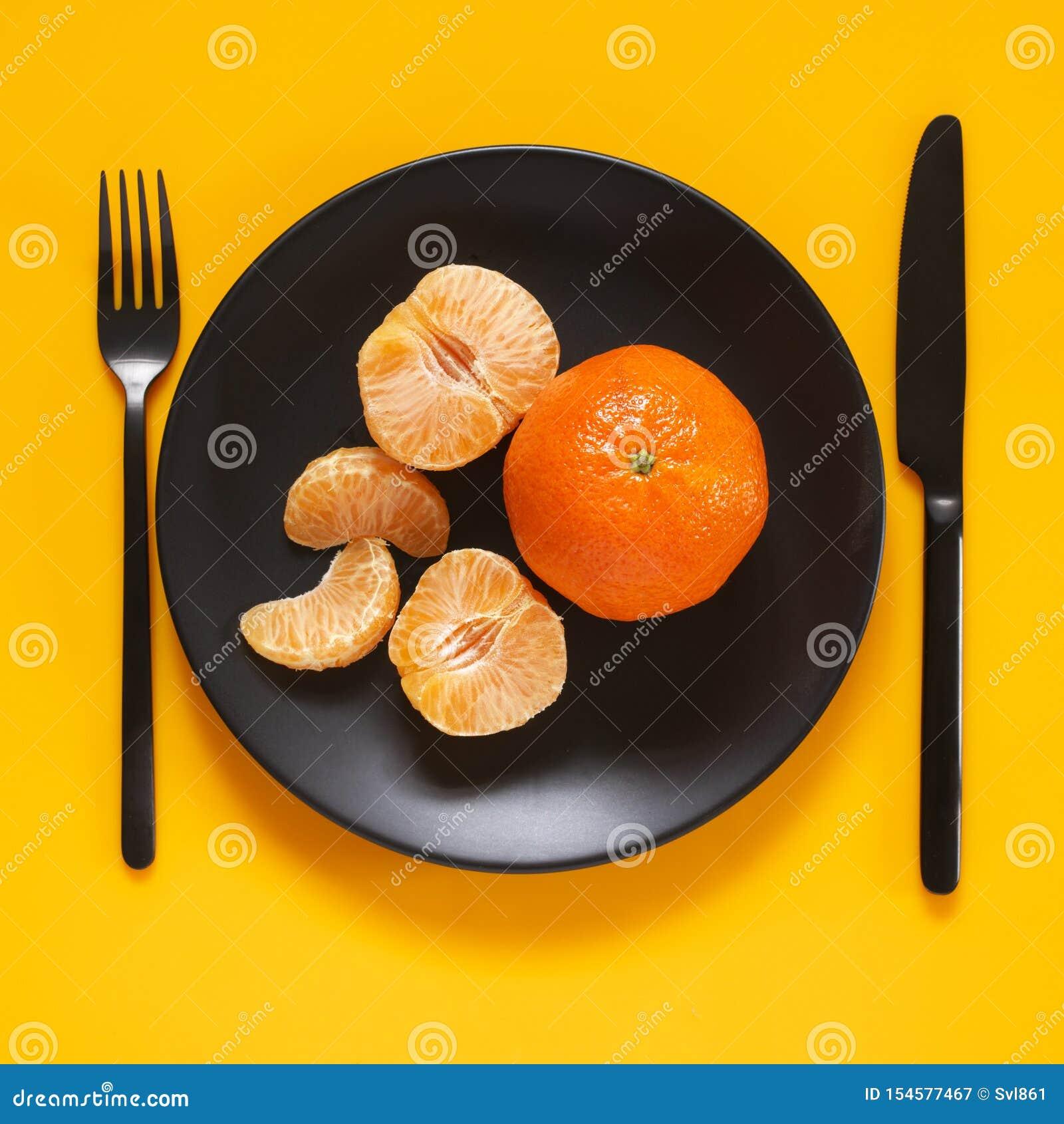 Tangerines в черной плите на желтом цвете