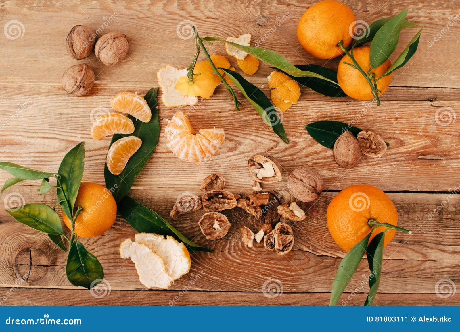 Tangerines с зелеными листьями на деревянной предпосылке