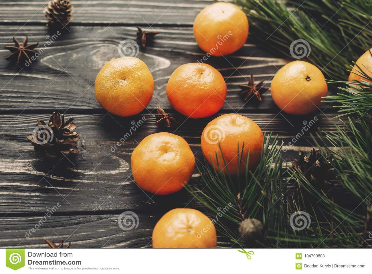 tangerines and fir branches anise and pine cones on rustic wooden background. merry christmas, seasonal greetings, happy holidays