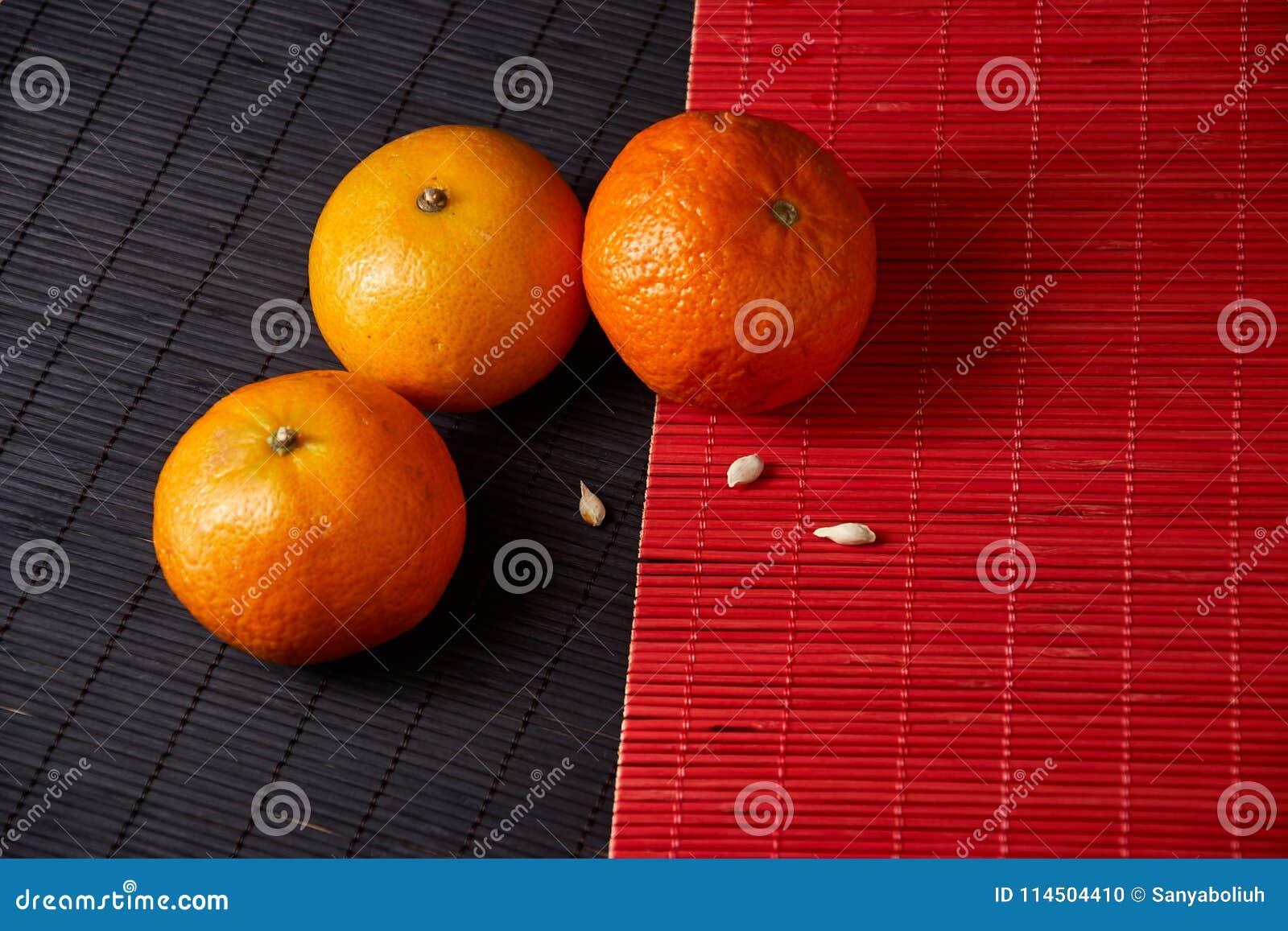 Tangerines mandarynki, clementines, cytrus owoc na stylowym czarnym i czerwonym tle z kopii przestrzenią