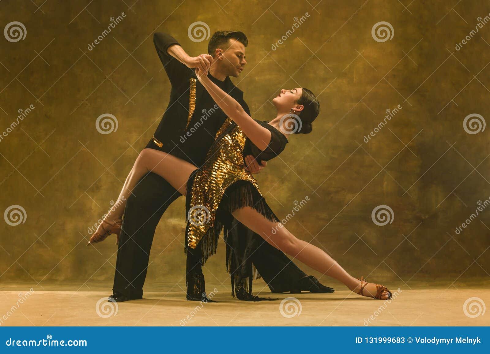 Taniec sala balowej para w złoto sukni tanu na pracownianym tle