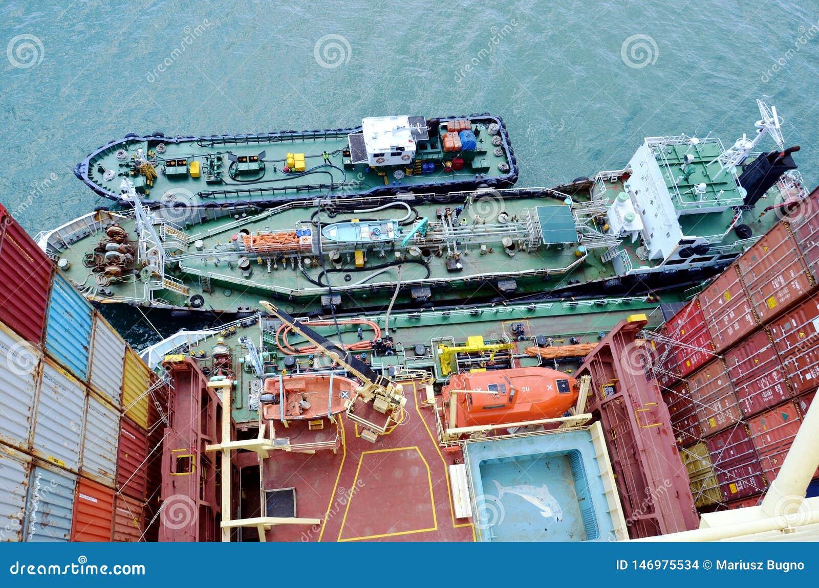 Tanker längsseits des großen Containerschiffs