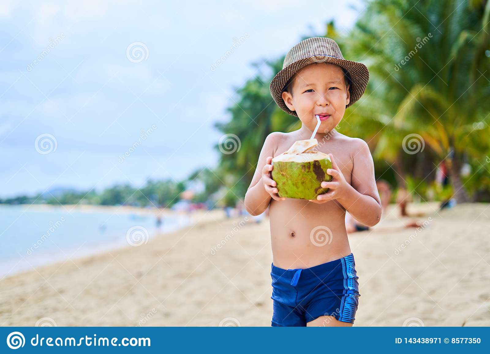 Tanned Asian boy stands on the beach in a hat and drinks coconut