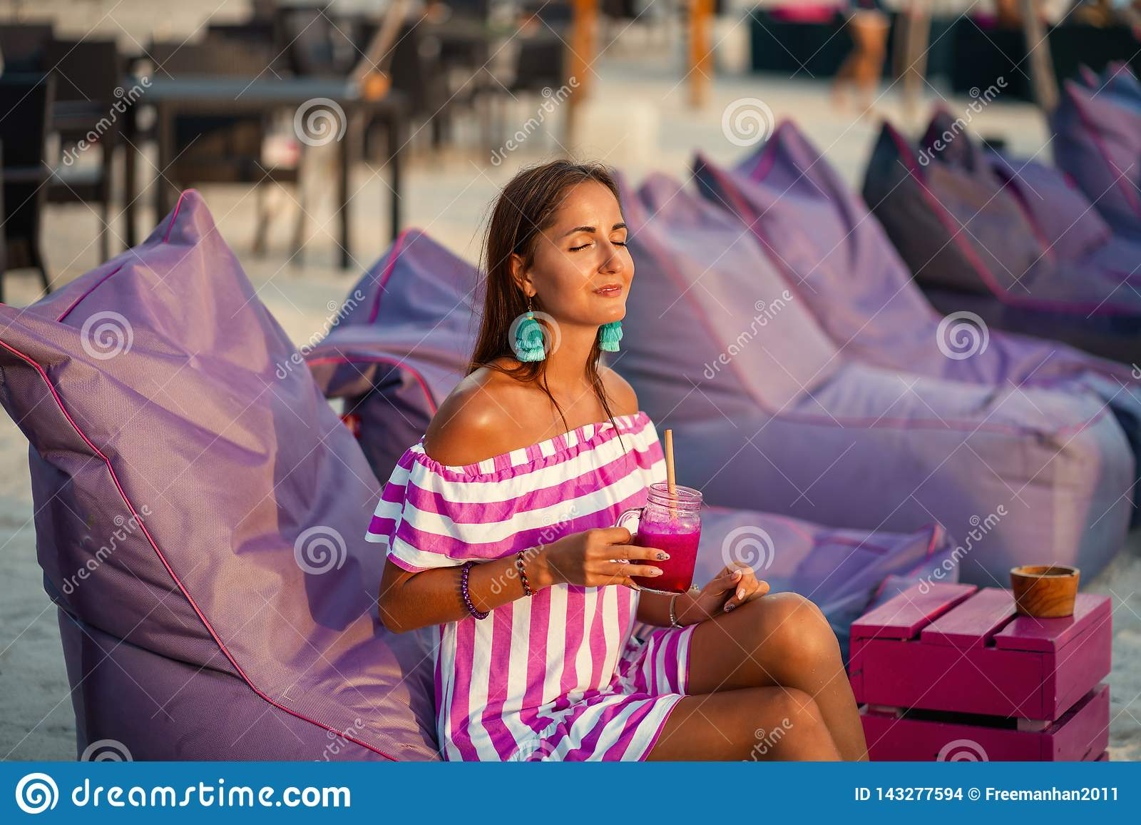 Tanned beautiful woman resting on the beach sofas and drinking a cocktail. Girl smiles and enjoys the sun. Spa and relax concept