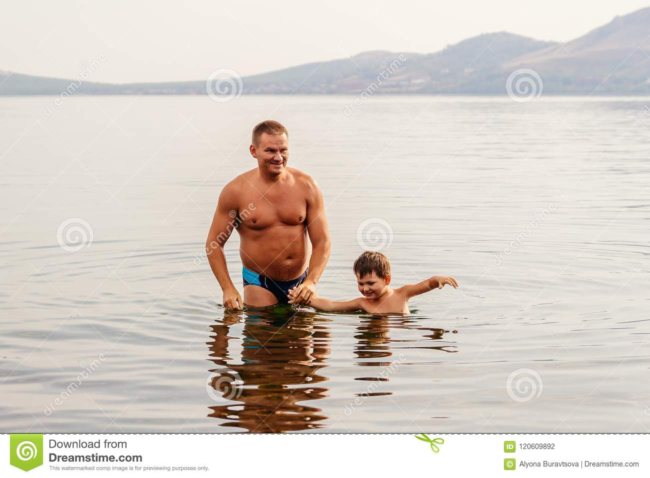 181bb787ef Tanned father and happy son in swimming trunks stand in the lake, holding  hands