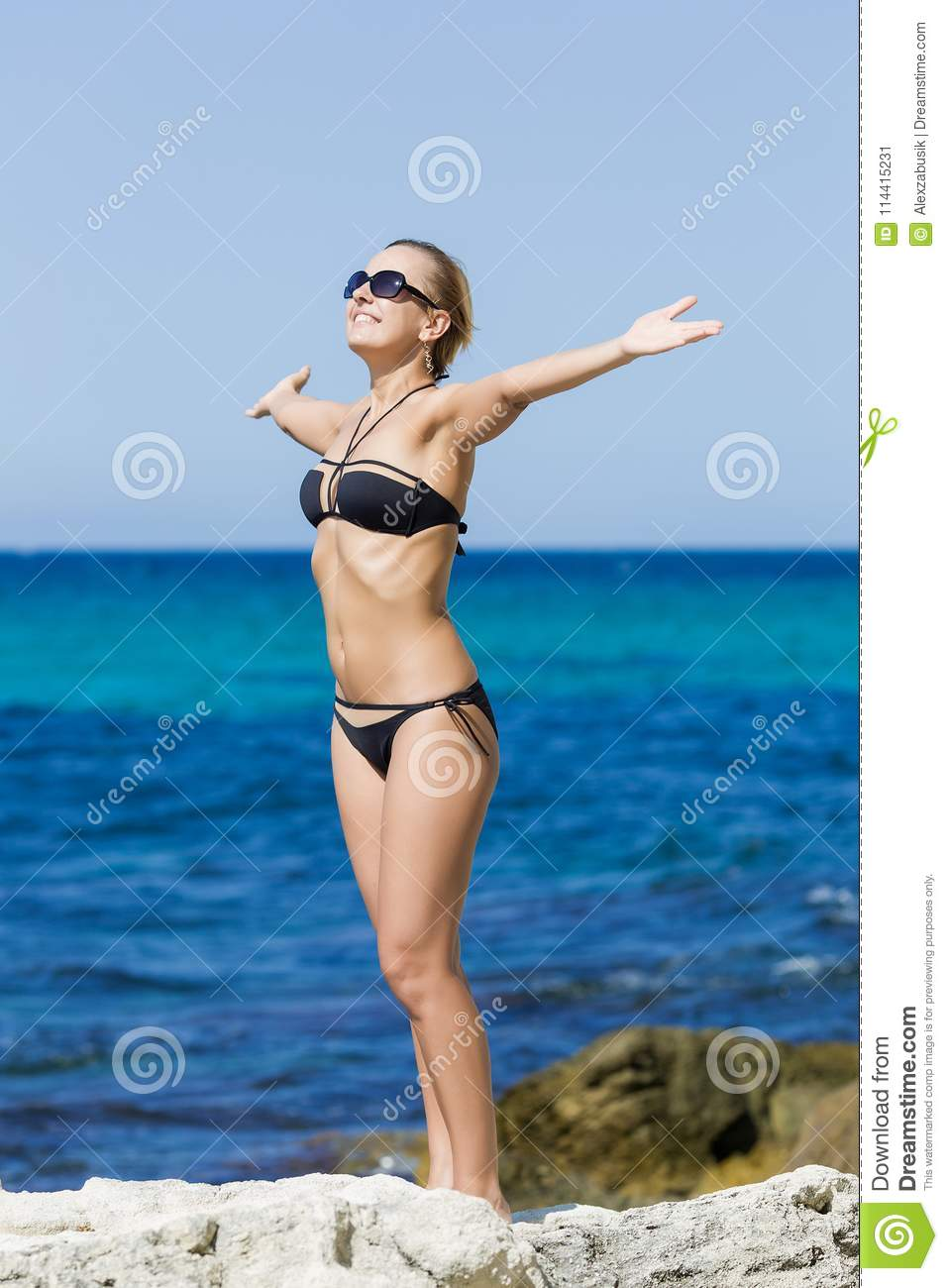 Tanned girl in swimsuit posing with arms outstretched against se