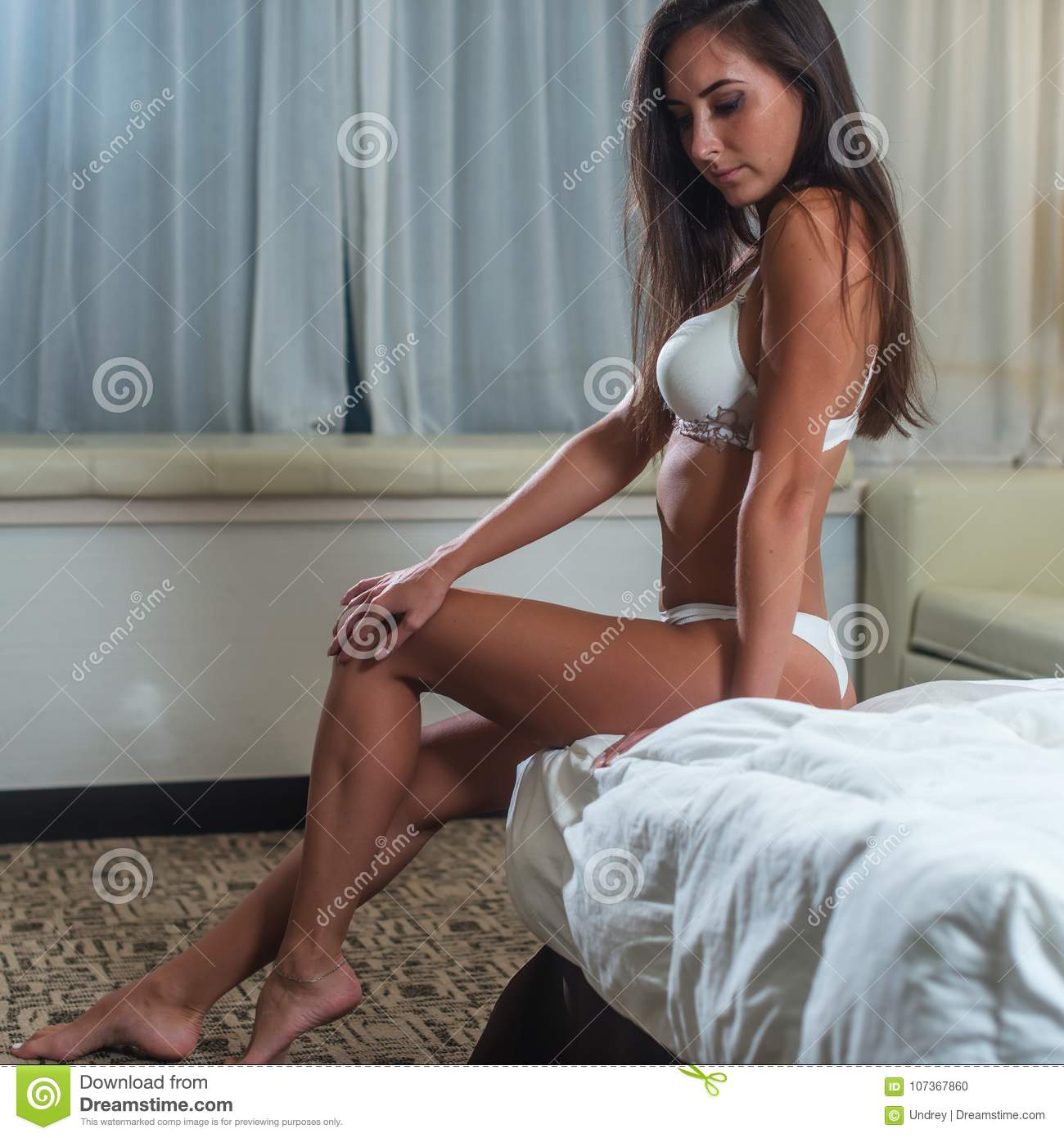 Tanned slim young brunette woman wearing white bra posing sitting on bed in light bedroom