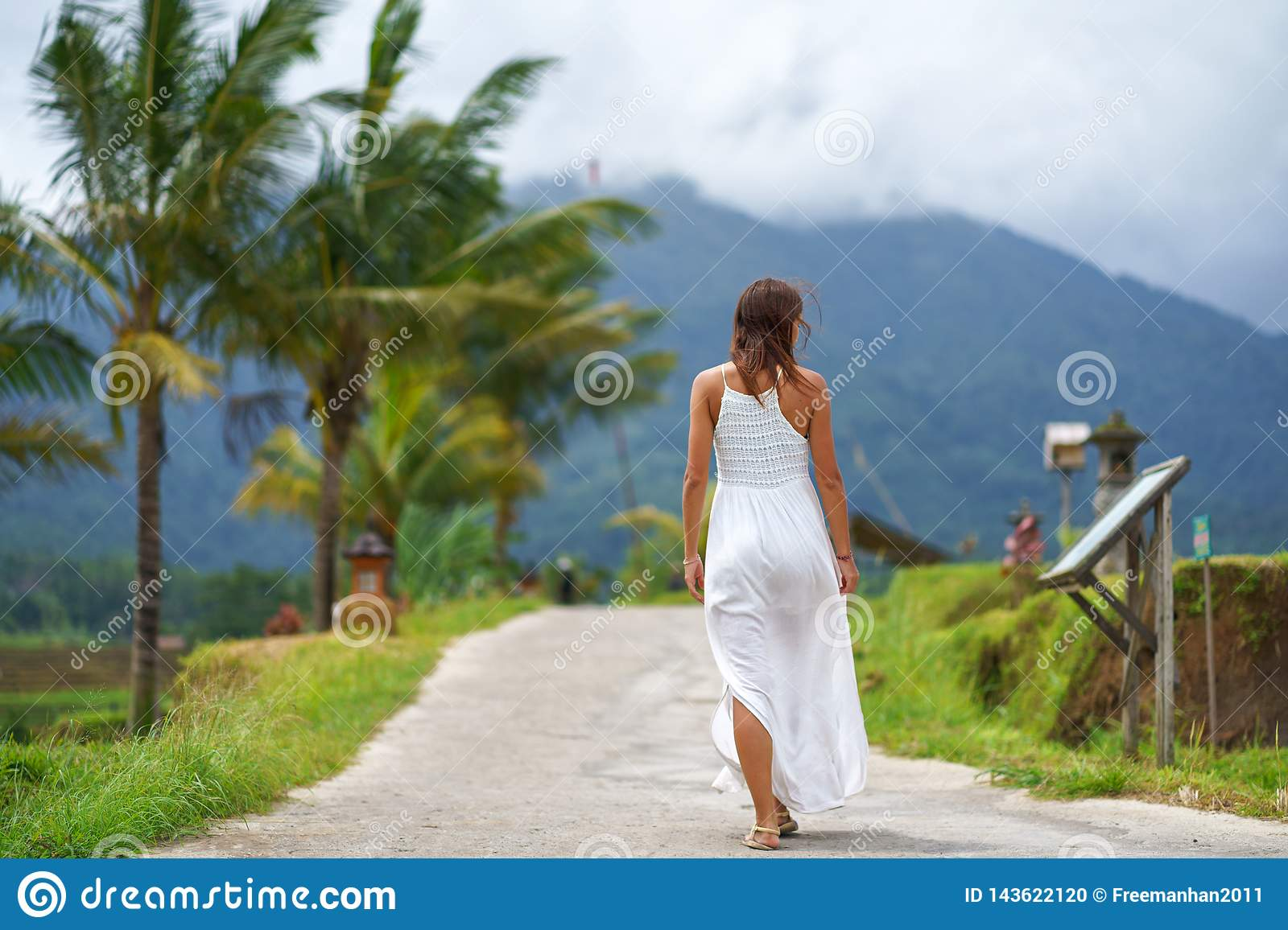 A tanned woman in a white dress walks forward on the road. The view from the back. In the background, a mountain in the fog and