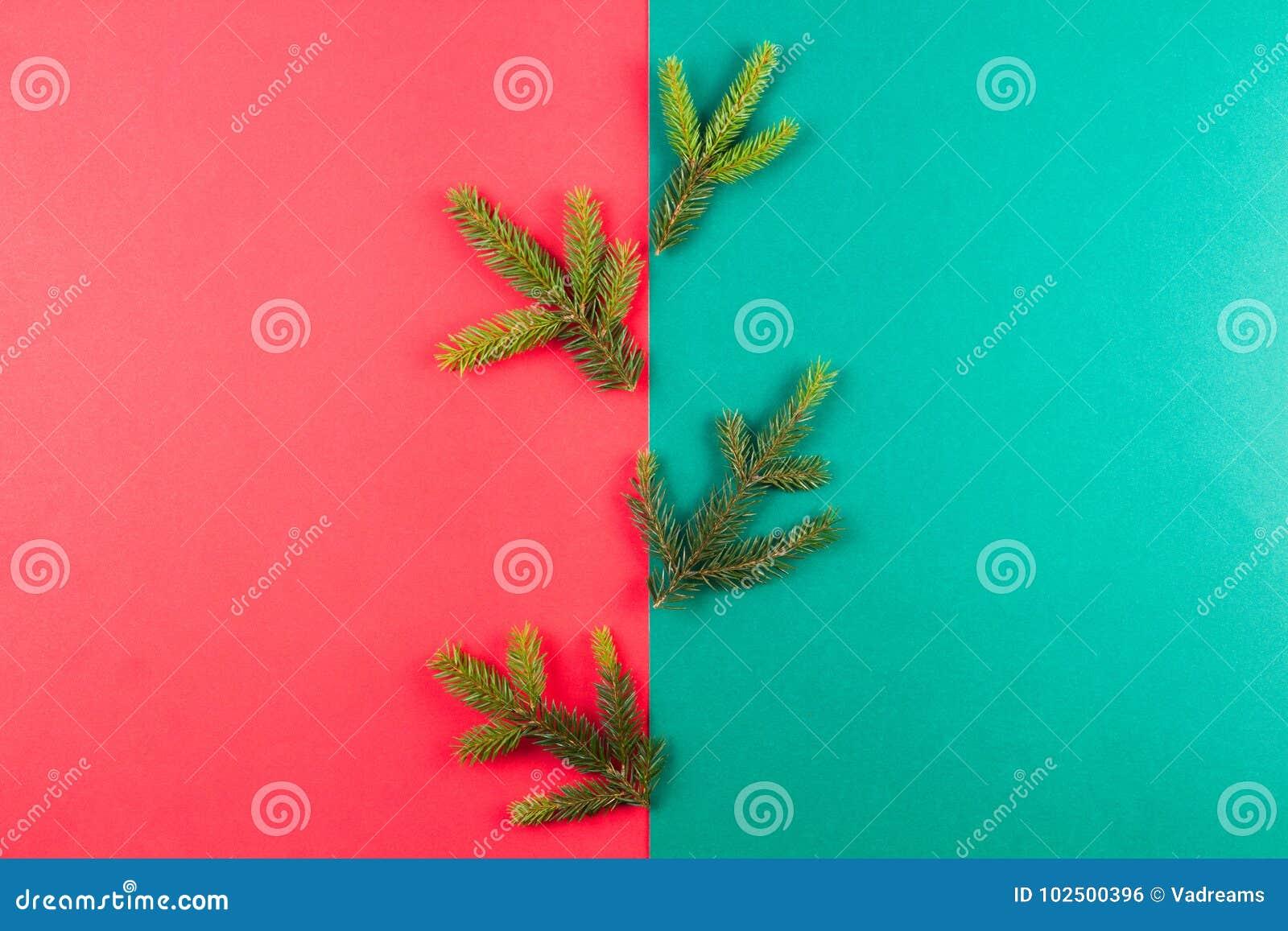Tannenbaumast auf rotem und grünem Hintergrund Flitter in einem blauen Glas