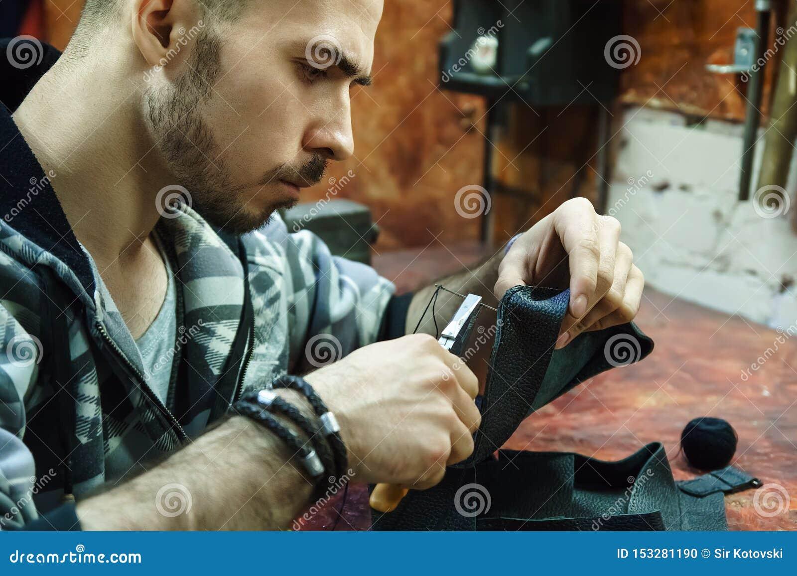 Tanner sews leather item in workshop.