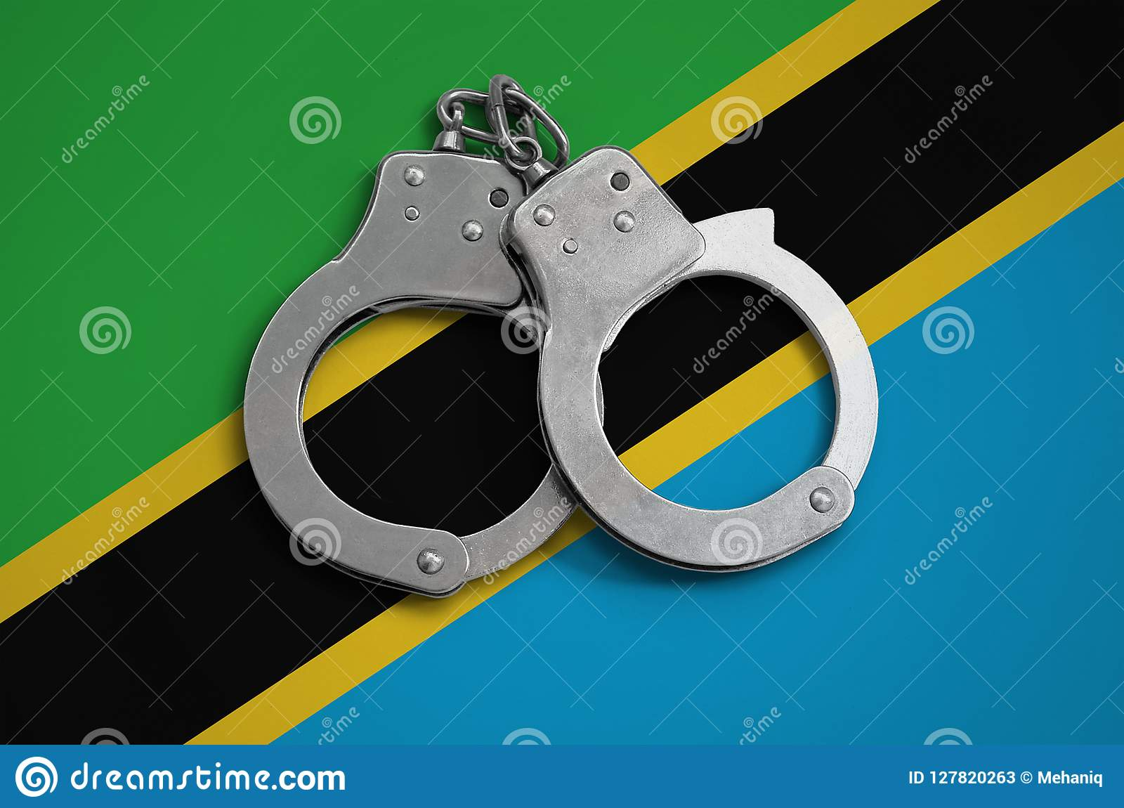Tanzania flag and police handcuffs. The concept of observance of the law in the country and protection from crime