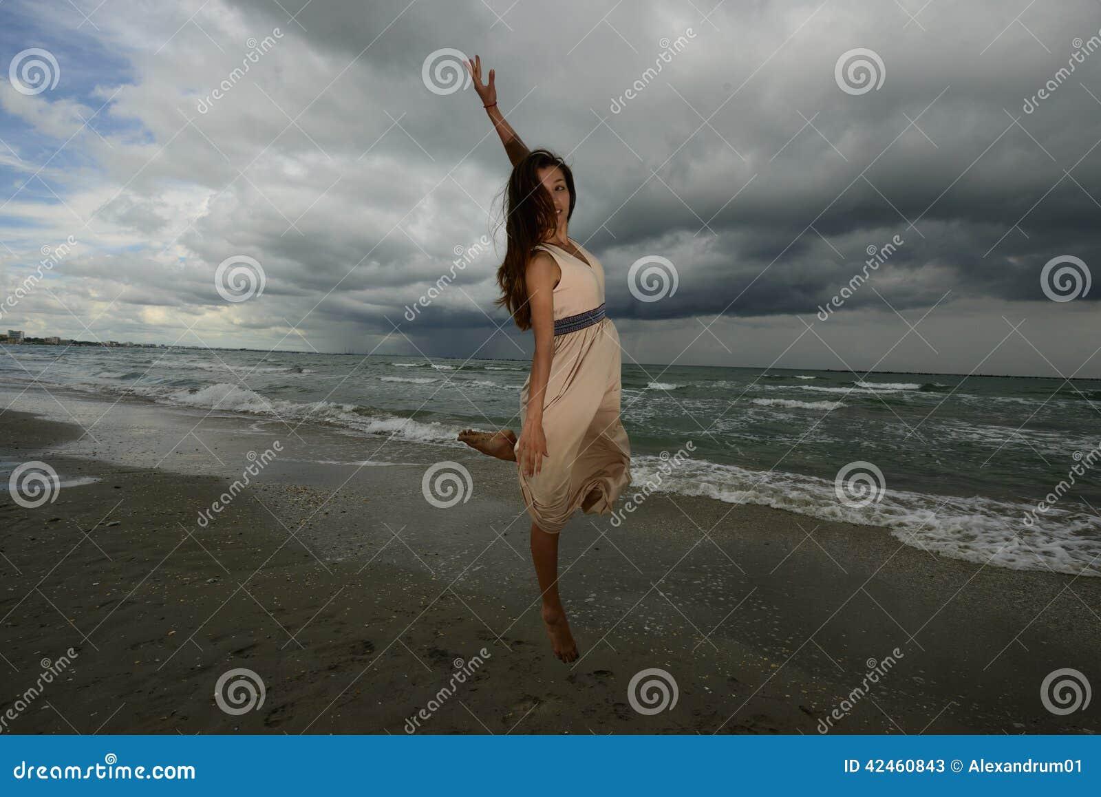 Tanzen der jungen Frau auf einem Strand