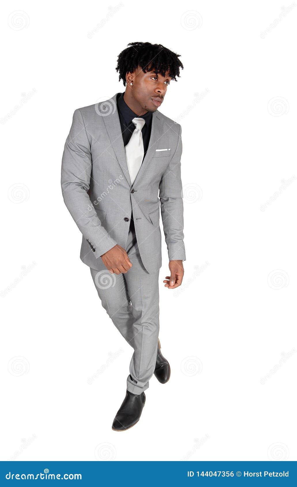 Tanzender schwarzer Mann in einem grauen Anzug mit dem unnötig geschäftigen schwarzen Haar