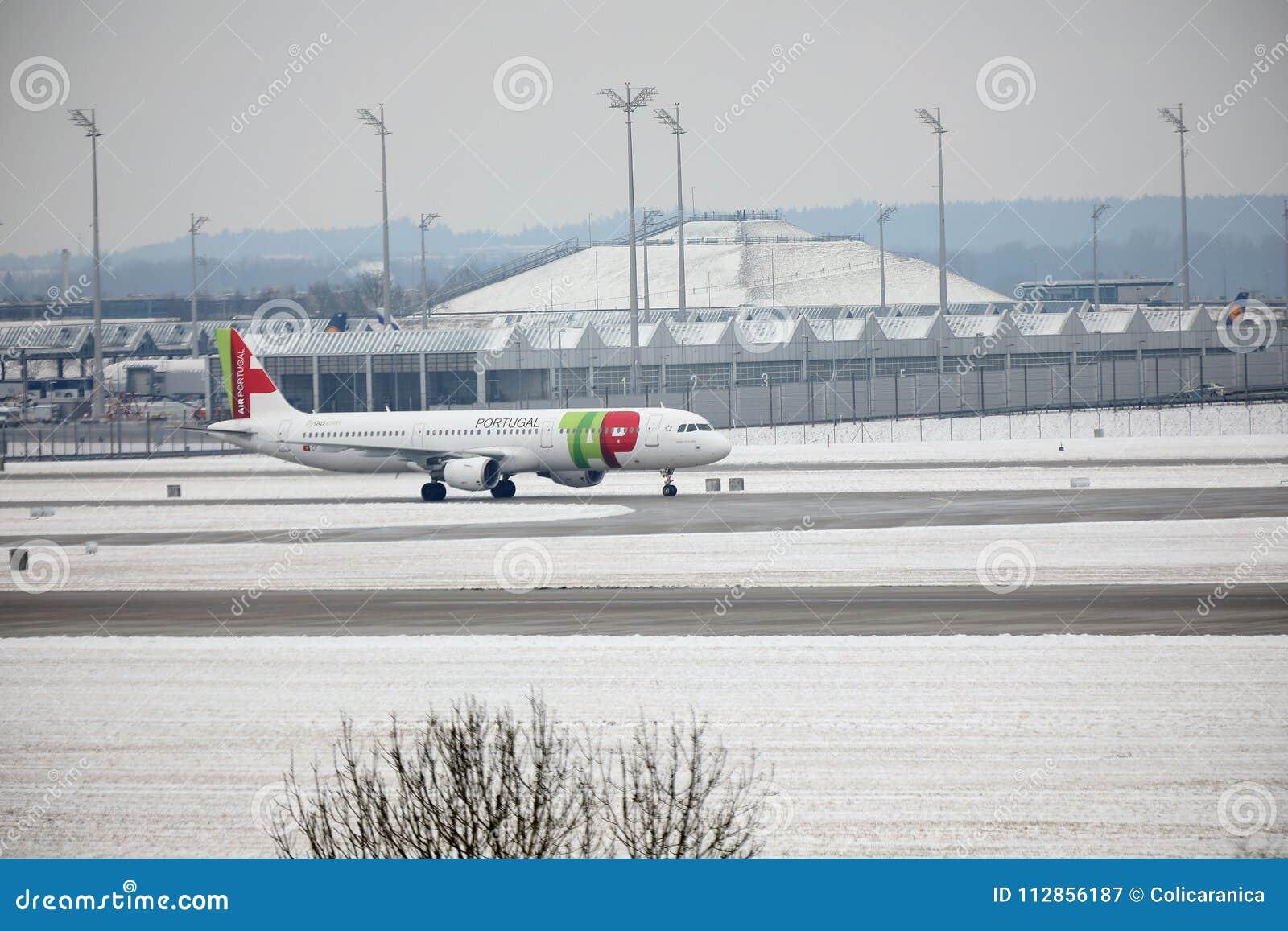 TAP het vliegtuig van Luchtportugal op baan in de Luchthaven van München, Duitsland, de Wintertijd met sneeuw