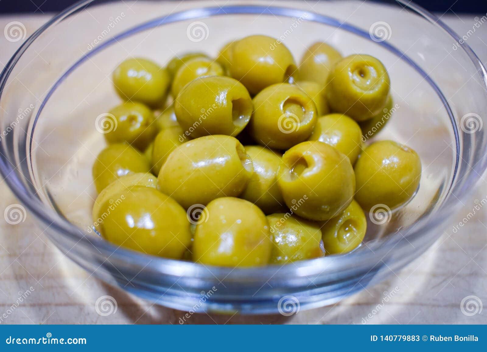 Tapa zielone oliwki wypełniał sardela w przejrzystym szklanym pucharze właśnie słuzyć jedzącym na stołowym