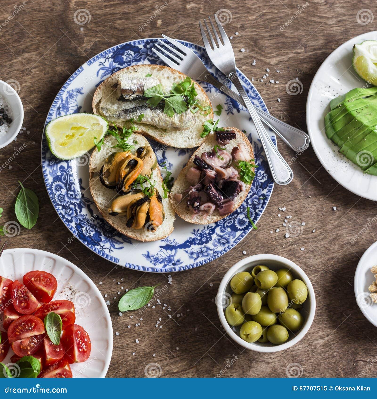 Tapas délicieux - sandwichs avec des sardines, des moules, le poulpe, le raisin, la tomate et l avocat sur la table en bois