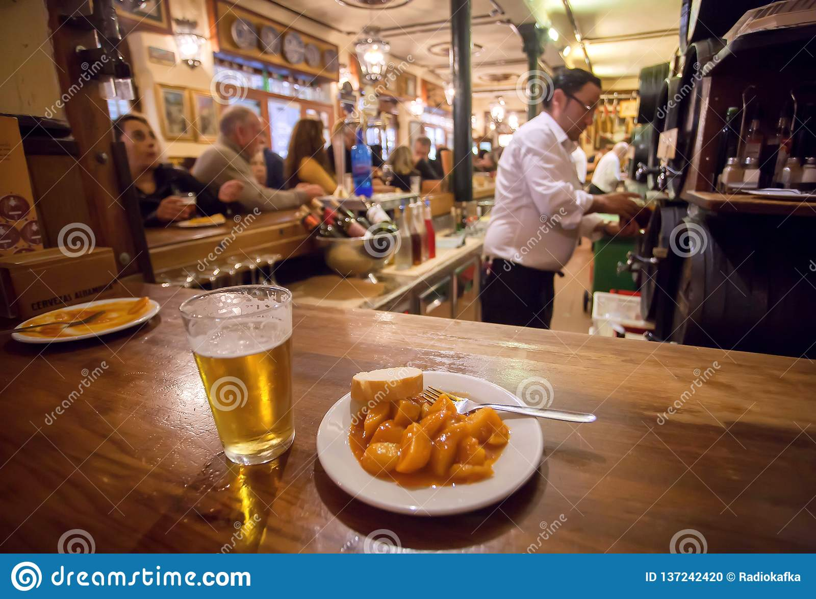 Tapas da batata na placa e no vidro da cerveja para o cliente do restaurante de comida rápida ocupado no estilo espanhol tradicio