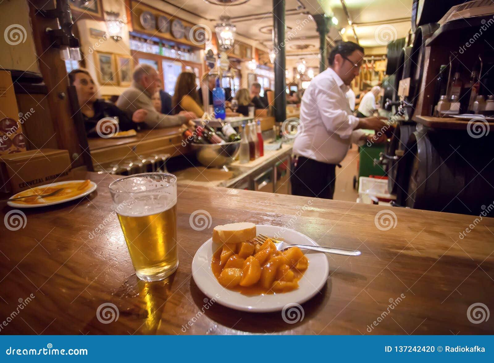 Tapas de la patata en la placa y el vaso de cerveza para el cliente del restaurante de comida rápida ocupado en estilo español tr