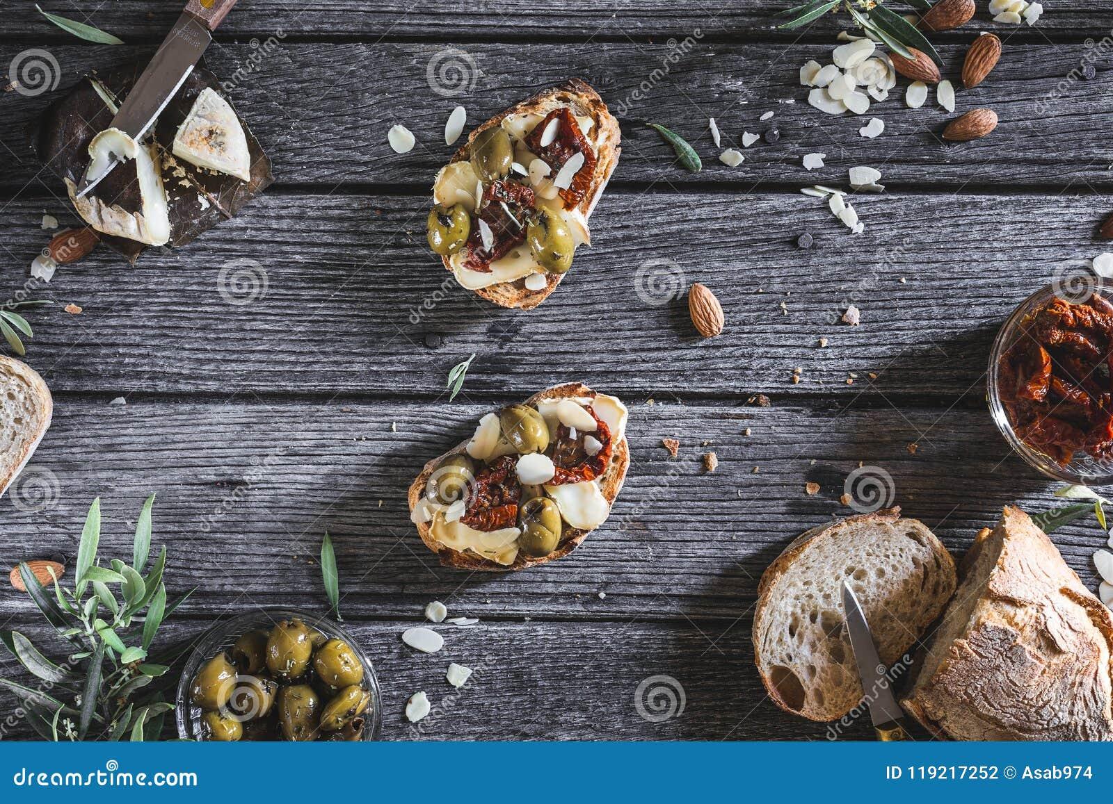 Tapas vegetariani del pane delle mandorle con i pomodori, l oliva verde, il formaggio e le mandorle secchi per brunch