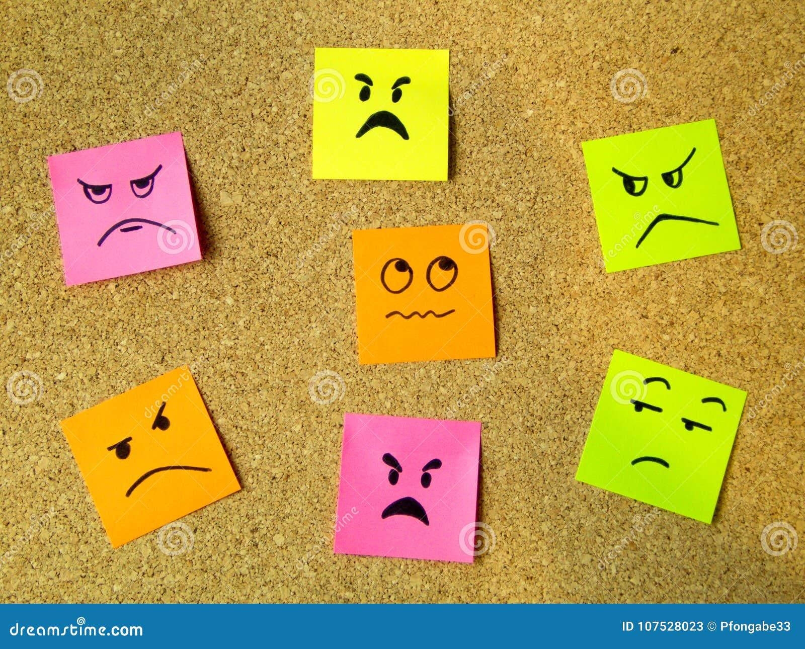 Tape al tablero con corcho con los post-it coloridos que representan diversos emoticons con la comunicación de la emoción de la c