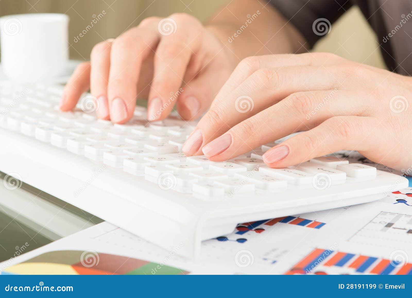 Taper sur le clavier. Mains de femme, vue proche