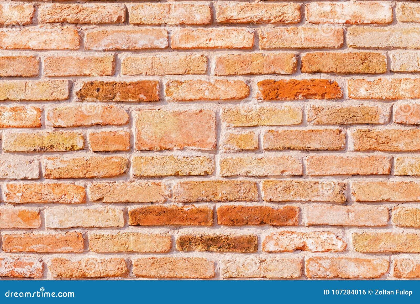 Tapete einer roten antiken Backsteinmauer mit farbigen Ziegelsteinen