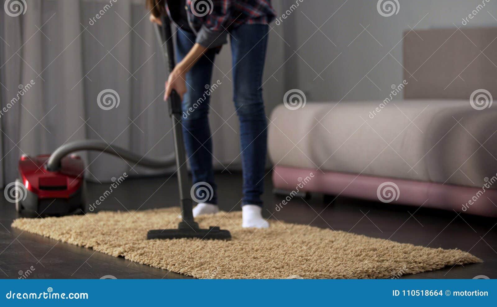 Tapete hoovering fêmea da sala durante a limpeza geral, funcionamento da casa, limpeza
