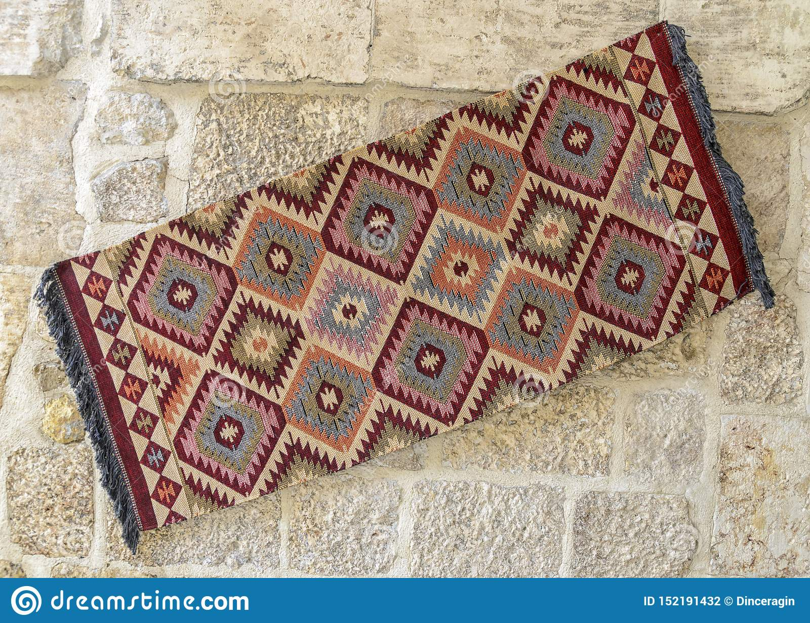 Tapetes turcos brilhantes que penduram em uma parede de pedra