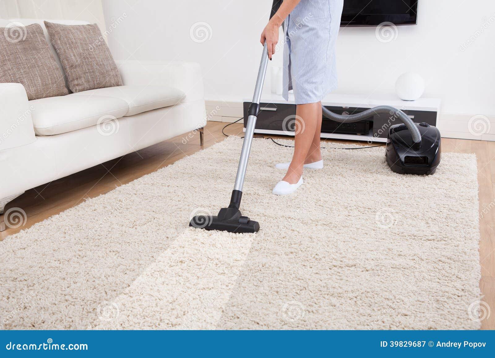Tappeto di pulizia della domestica con l aspirapolvere