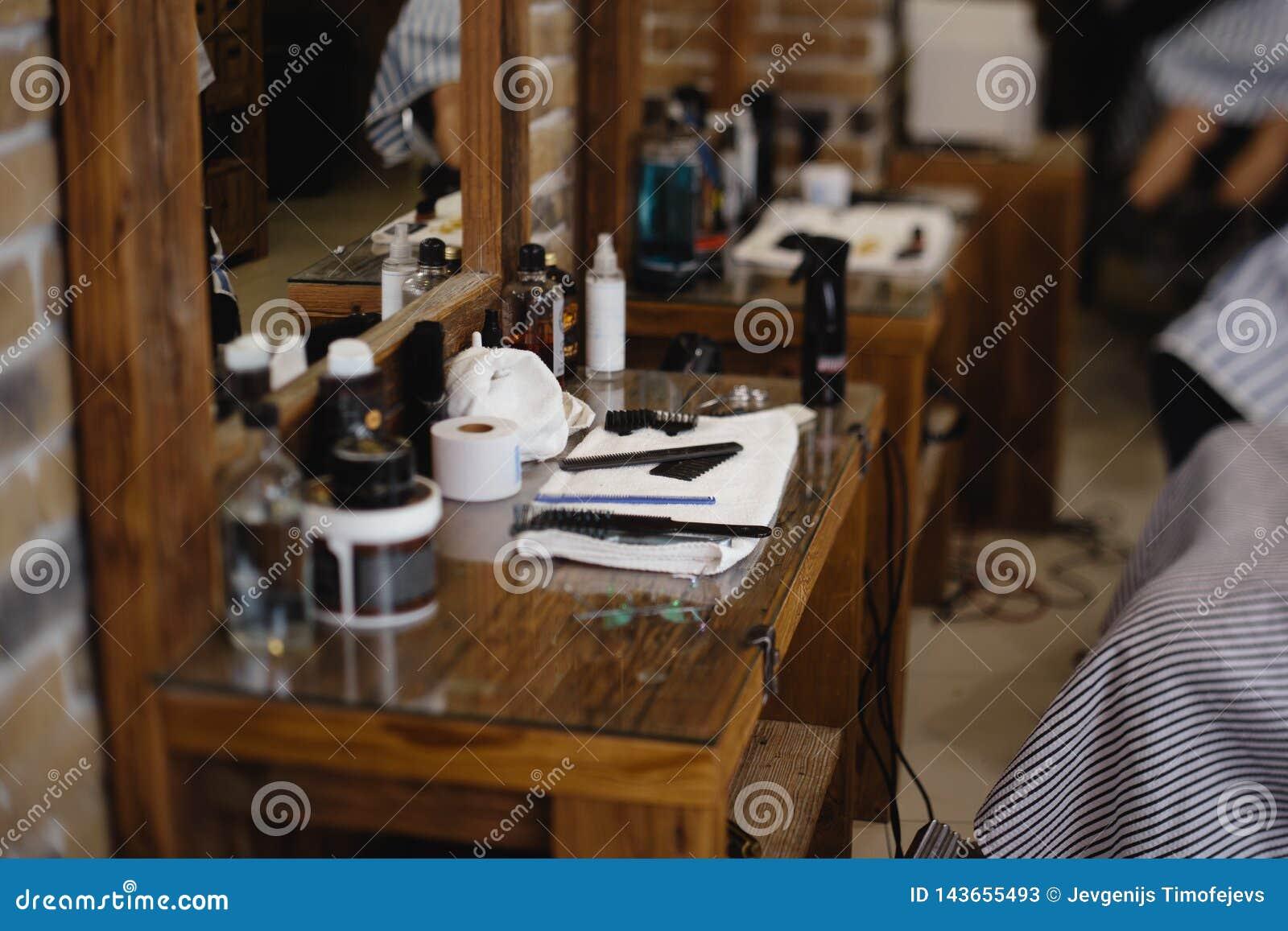 Tappningbarberare- eller rakapparathjälpmedel på trätabellen i en frisersalong