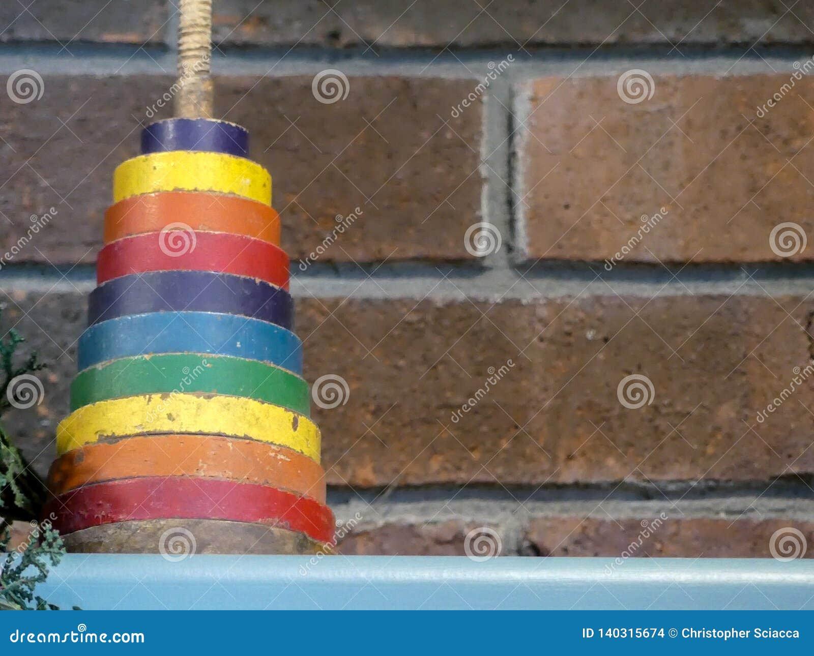 Tappningbarns leksak mot tegelstenbakgrund Sortiment av färg